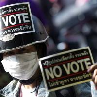 Poll position: A Thai anti-government protester holds a placard during a rally in Bangkok on Saturday. | AFP-JIJI