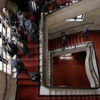 Downward spiral: Prime Minister Shinzo Abe (left) walks down the stairs while talking on a mobile phone after attending a lower house budget committee session at the Diet in Tokyo. | REUTERS