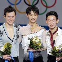 Gold medalist Yuzuru Hanyu is flanked by silver medalist Patrick Chan (left) and bronze-medalist Denis Ten after the figure skating men's free skating program Friday night. | KYODO