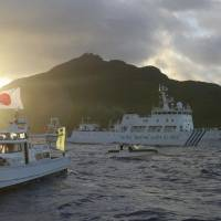 Tension on the high sea: Members of the Japan Coast Guard watch as a Chinese surveillance vessel passes near Uotsuri Island, part of the Senkaku Islands in the East China Sea, in July 2013. | KYODO