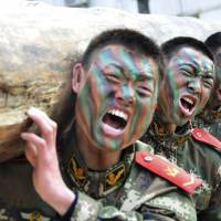 Chinese troops lift a log during a training session in January at a base in Chaohu, Anhui province. | REUTERS