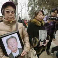 Relatives of Chinese citizens forced into wartime labor for Japanese companies walk to the Beijing No. 1 Intermediate People's Court on Wednesday to file a lawsuit. | KYODO