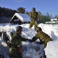 Ground Self-Defense Force personnel dig a car out of the snow in a Yamanashi Prefecture neighborhood Sunday. | GSDF/REUTERS