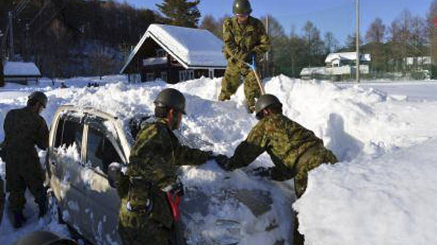 Ground Self-Defense Force personnel dig a car out of the snow in a Yamanashi Prefecture neighborhood Sunday.