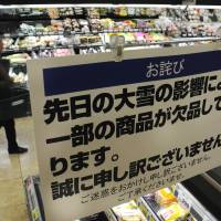 A supermarket in Tokyo displays a sign telling shoppers some food products are in short supply because of the recent heavy snowfall. | SATOKO KAWASAKI