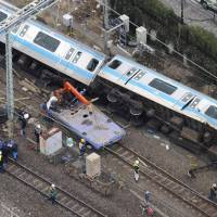 A derailed Keihin Tohoku Line train lies near JR Kawasaki Station after hitting a maintenance car Sunday. | KYODO