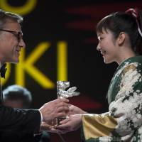 Kudos: Actress Haru Kuroki receives the Silver Bear for best actress at the 64th Berlin International Film Festival on Saturday, for her part in director Yoji Yamada's 'The Little House.' The Berlinale, Europe's first major film festival of the year, ended Sunday. | AFP-JIJI