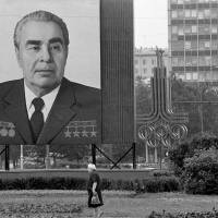Imposing view: A woman walks past a huge portrait of Communist Party chief Leonid Brezhnev that dwarfs the symbol of the Moscow Summer Olympics in the Soviet capital in July 1980. Brezhnev and his ruling Politburo wanted the games to legitimize the Soviet system, a military superpower and economic basket case. | AP