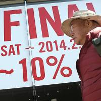 A man walks past a Tokyo clothing store advertising a winter sale in January. | AP
