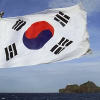 Sea row: A South Korean flag flaps on a boat near islets called Dokdo in Korean and Takeshima in Japan in August 2012. | AP