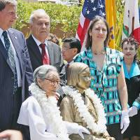 """Kim Bok-dong, who spent eight years as a """"comfort women"""" for the Imperial Japanese Army, sits next to a bronze statue dedicated to the wartime sex slaves at Glendale Central Park near Los Angeles at the memorial's unveiling last July.  