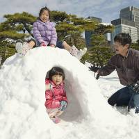 Snow job: A family builds an igloo Sunday at the Imperial Palace in Tokyo, after the city's heaviest snow since 1969. | KYODO