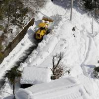 Houses in Hayakawa, a remote town in Yamanashi Prefecture, are surrounded by snow on Monday, preventing residents from acquiring necessities or receiving assistance. | KYODO