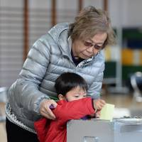 By proxy: A boy casts a ballot for his grandmother Sunday in Tokyo for the gubernatorial election. | AFP-JIJI