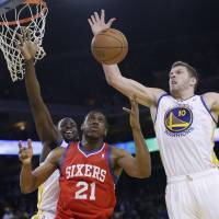 Not time to rest: Golden State's David Lee grabs a rebound next to Philadelphia's Thaddeus Young (21) and teammate Draymond Green during first-half action on Monday in Oakland, California. | AP