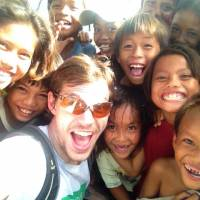 Group selfie: Dean Newcombe meets local children on a relief mission in the Philippines in the wake of Typhoon Haiyan, which laid waste to parts of the country in November. | COURTESY OF INTREPID MODEL ADVENTURES