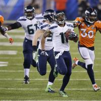 Just passing through: Seattle's Percy Harvin leads the pack as he runs toward the end zone during his 87-yard kickoff return to open the second half of Super Bowl XLVIII on Sunday. | AP