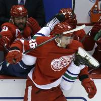 Deep in enemy territory: Red Wings winger Tomas Jurco checks Canucks defenseman Alexander Edler into the Detroit bench during their game on Monday. The Red Wings won 2-0. | AP