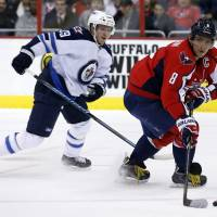 Capital gains: Washington's Alex Ovechkin looks to pass the puck as the Jets' Tobias Enstrom gives chase on Thursday in Washington. The Capitals won 4-2. | AP
