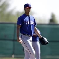 Back to business: Yu Darvish sweeps dirt off the rubber during a Rangers intrasquad game on Monday. | AP