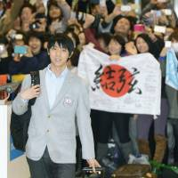 Home sweet home: Fans cheer as men's figure skating gold medalist Yuzuru Hanyu walks through Narita airport after returning from the Sochi Olympics on Tuesday. | KYODO