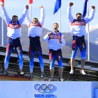 The hosts with the most: The Russian four-man bobsled team celebrates after winning the gold medal on Sunday. Their win helped Russia top the medals table. | AFP-JIJI