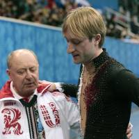 Not in the script: Evgeni Plushenko is helped off the ice by his coach, Alexei Mishin, after pulling out of the men's short program at the Sochi Olympics on Thursday. | AP