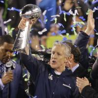 We are the champions: Coach Pete Carroll holds up the Lombardi Trophy after leading Seattle to its first title. | AP