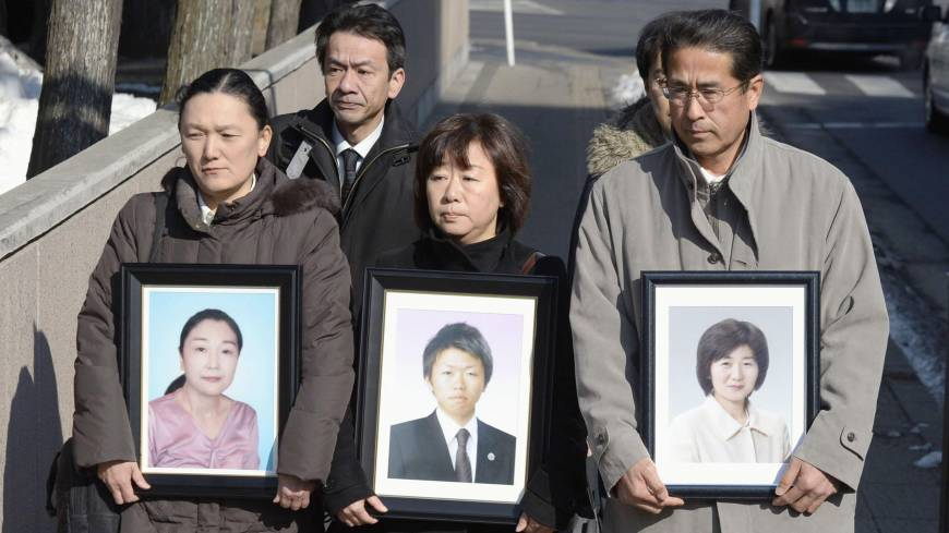 Relatives of three bank employees killed by the March 11, 2011, tsunami hold photos of their loved ones as they enter the Sendai District Court on Tuesday.