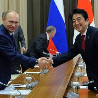 Comrades: Russian President Vladimir Putin greets Prime Minister Shinzo Abe at the Bocharov Ruchei residence in Sochi, Russia, on Saturday. | AP/RIA-NOVOSTI, MIKHAIL KLIMENTYEV, PRESIDENTIAL PRESS SERVICE
