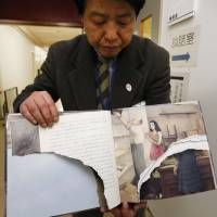 A librarian in Tokyo's Suginami Ward holds a vandalized copy of Anne Frank's 'A Diary of a Young Girl' on Wednesday. | KYODO