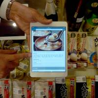 The main ingredients: A Sato Holdings official displays a bar code system that can display multilingual information on Japanese food products recently at Iwate Ginza Plaza in Tokyo's Ginza district. | SATO HOLDINGS