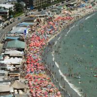 People crowd Zushi beach in Kanagawa Prefecture last August. | KYODO