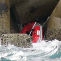 Mystery find: A dinghy in which the body of a Cabinet Office staffer was spotted sits in a breakwater Jan. 18 near Kitakyushu. | WAKAMATSU COAST GUARD/KYODO
