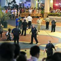 Scene of the crime: Police secure the scene after Chad Ryan De Soto, then 21, drove a Toyota car through a crowd of people in Guam's shopping district on Feb. 12, 2013. | AP/KYODO