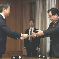 Exiting: Osaka Mayor Toru Hashimoto (left) submits his resignation Friday to Yoshinobu Kinoshita, head of the municipal assembly. | KYODO