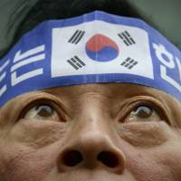 A protester wears a headband that reads 'Dokdo is Korean territory' during a march over the disputed islets, which Japan claims as Takeshima, in front of the Japanese Embassy in Seoul on Saturday. | AFP-JIJI
