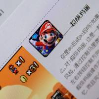 "The download page for a copycat ""Mario"" game on the Beijing Flyfish Technology Co. website is shown on a smartphone. 