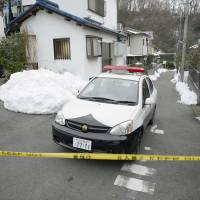 Off-limits: A police officer stands watch near the scene where a man allegedly stabbed a 17-year-old girl to death in Hachioji, Tokyo, on Thursday. | KYODO