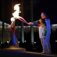 Let it burn: Vladislav Tretiak and Irina Rodnina light the cauldron during the opening ceremony on Friday in Sochi, Russia. | AP