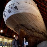 Matashichi Oishi, a former crew member of the Fukuryu Maru No. 5, stands with his daughter, Yoshiko Tanaka, in front of the trawler preserved at the Daigo Fukuryu Maru Exhibition Hall in Koto Ward, Tokyo. | KYODO