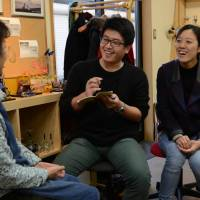 Meet the neighbors: Chinese exchange students Yin Yong Ming (center) and Wang Dan (right) interview a resident of Hikone, Shiga Prefecture, in fluent Japanese. | CHUNICHI SHIMBUN