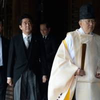 Making waves: A Shinto priest leads Prime Minister Shinzo Abe as he visits Yasukuni Shrine in Tokyo on Dec. 26. | AFP-JIJI
