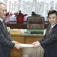 Shigeyuki Goto, then senior vice minister of justice, receives a request on Feb. 8, 2013, to revise the juvenile law from Makoto Ito (left), chairman of the legislative council of the Justice Ministry. | KYODO