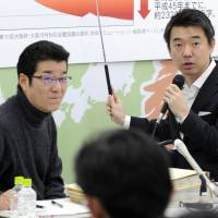Osaka Mayor Toru Hashimoto (right) explains to the media in Osaka on Feb. 15 his plan to integrate the city of Osaka and Osaka Prefecture, as Osaka Gov. Ichiro Matsui looks on. | KYODO