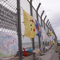 The perimeter fence for U.S. Marine Corps Camp Schwab on Henoko beach in Nago, Okinawa Prefecture, is draped with anti-U.S. base protest banners on Feb. 6. | AP