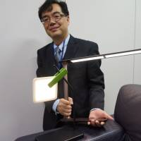 Sleek design: Yasuki Kawashima of NEC Lighting Ltd. shows off an OLED desk lamp. | KAZUAKI NAGATA