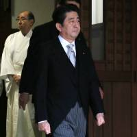 Courting controversy: Prime Minister Shinzo Abe leaves Yasukuni Shrine in Tokyo after paying tribute to the war dead enshrined there on Dec. 26. | BLOOMBERG