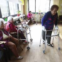 Kim (right) passes by other comfort women Yi Ok-seon, 88 (far left) and Kim Wei-han, 86. | AP