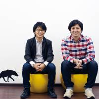 Takuma Kobayashi (left), the president of cloud funding firm Search Field Inc., and board member Ryuta Saito pose for a photo at the company's office in Shibuya Ward, Tokyo. | WEDGE